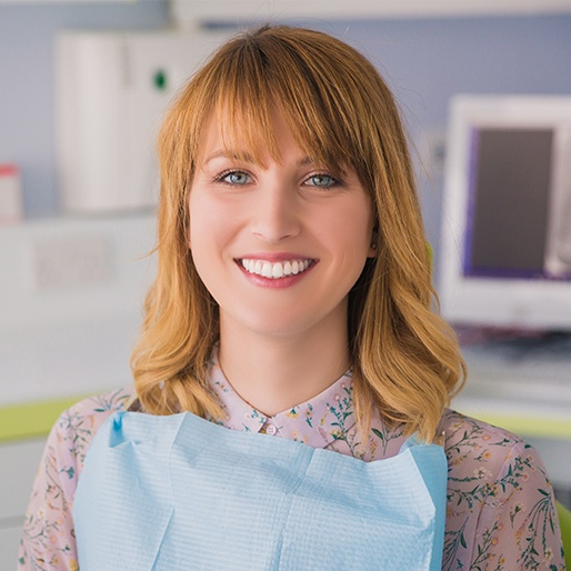 Woman in dental office sharing healthy smile
