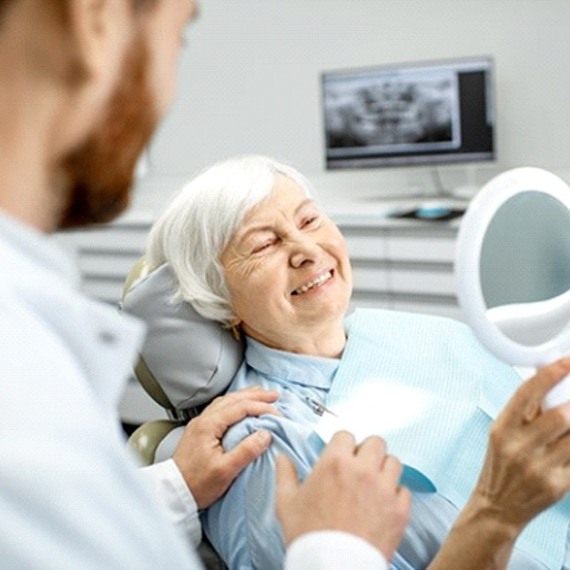 Smiling woman admiring her new dentures in Columbus