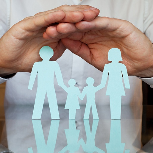 Hands protecting paper cut out family