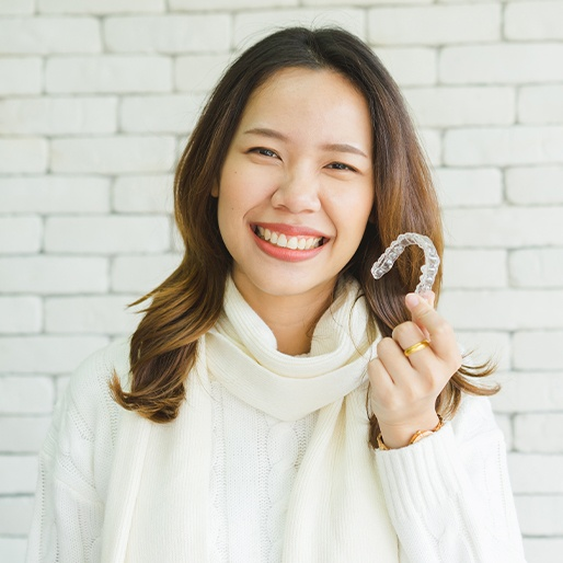 Smiling woman holding an Invisalign tray